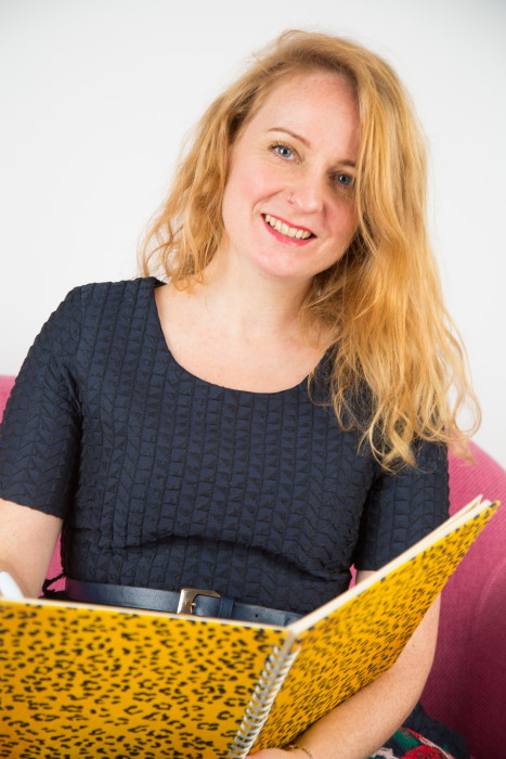 Image of Steph Cronin, Branding Specialist at Black Bee Creative. She is sat on a pink sofa looking straight at the camera holding a yellow leopard print notebook